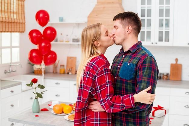 Vista lateral casal beijando na cozinha