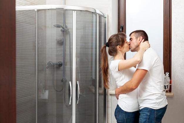 Vista lateral casal beijando no banheiro