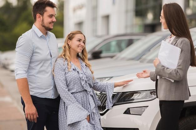 Vista lateral casal conversando com o negociante de carro feminino