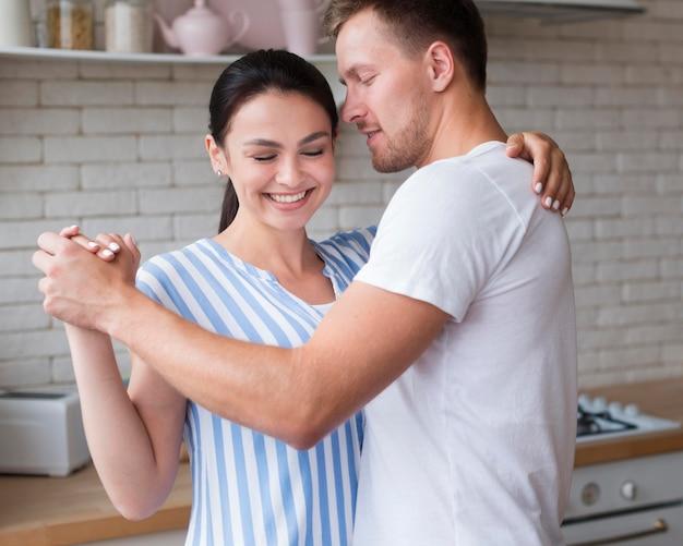 Vista lateral casal dançando dentro de casa