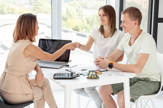 Vista lateral casal fazendo um acordo sobre sua nova casa