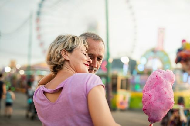 Vista lateral casal feliz com algodão doce rosa