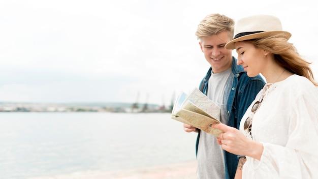 Vista lateral casal olhando para o mapa