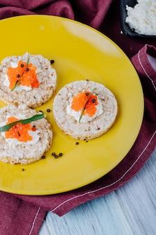 Vista lateral caviar vermelho aperitivo estaladiço crocante com queijo cottage tarhun de caviar vermelho e pimenta preta em um prato