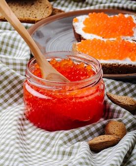 Vista lateral caviar vermelho torrada pão de centeio com queijo cottage caviar vermelho e amêndoa em cima da mesa