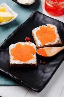 Vista lateral caviar vermelho torradas de pão de centeio com queijo cottage caviar vermelho e manteiga em cima da mesa