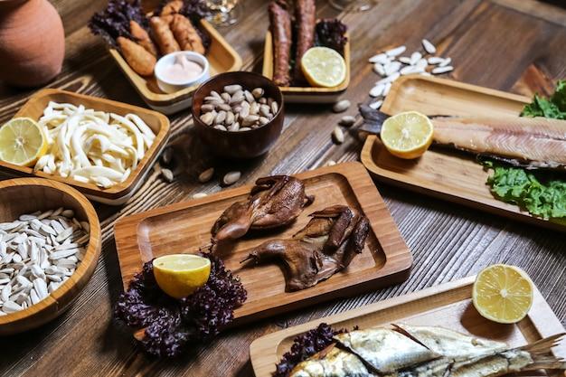 Vista lateral cerveja lanches peixe defumado codorniz defumado queijo trança sementes pistache com limão em cima da mesa