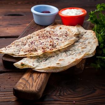 Vista lateral chebureks kutab fritos chebureks com queijo, ervas, carne com molho em uma mesa de madeira escura