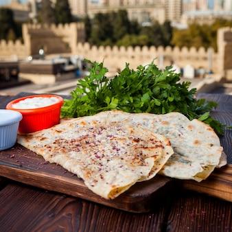 Vista lateral chebureks kutab pastéis fritos com queijo, ervas, carne com molho em uma mesa de madeira escura com vista cidade