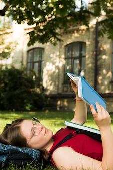 Vista lateral, cima, de, menina escola, lendo um livro
