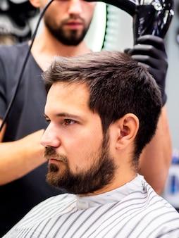 Vista lateral cliente cortando o cabelo