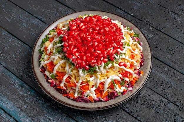 Vista lateral comida de natal salada de natal com batatas, cenoura, sementes de romã e molho no prato na mesa cinza