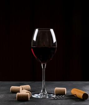 Vista lateral copo de vinho na mesa escura e vertical
