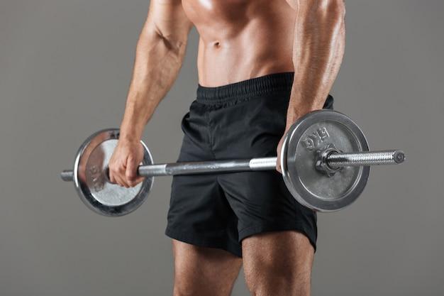 Vista lateral cortada a imagem de um fisiculturista masculino sem camisa forte