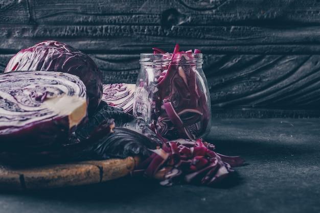 Vista lateral cortada em repolho roxo no frasco no plano de fundo texturizado escuro. vertical