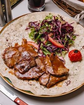 Vista lateral cozido lombo de carne em molho com salada de legumes no pão pita