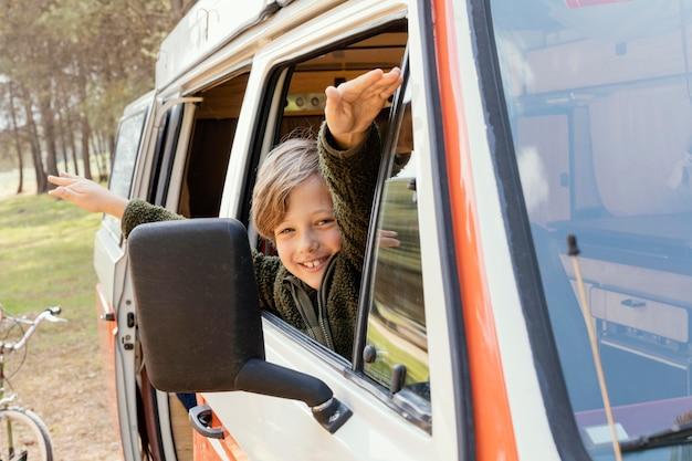 Vista lateral criança feliz olhando pela janela