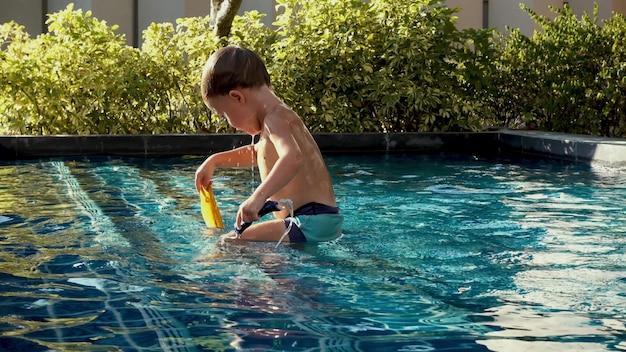 Vista lateral criança molhada em calções de banho tomando banho na piscina com água azul claro em dia ensolarado
