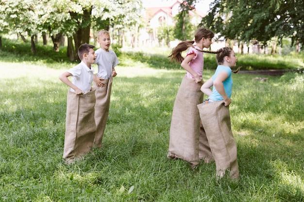 Vista lateral crianças brincando em sacos de aniagem
