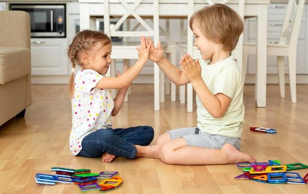 Vista lateral crianças em casa brincando