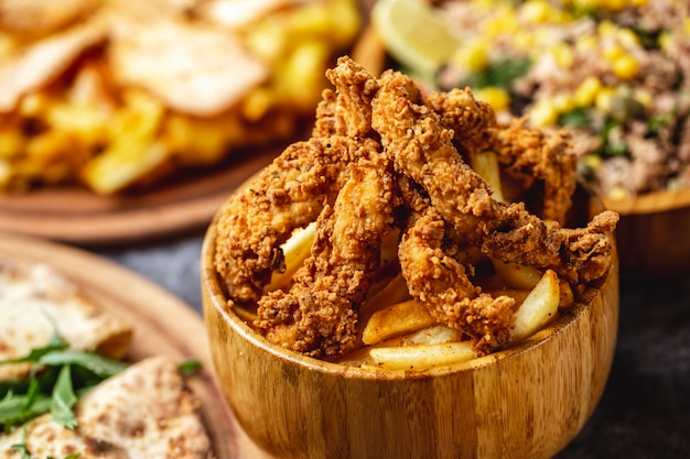 Vista lateral crocante de frango frito com batatas fritas