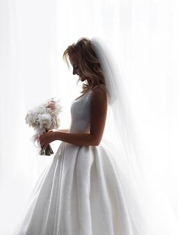 Vista lateral da adorável noiva, usando um vestido de noiva brilhante e véu, considerando as flores