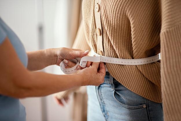 Vista lateral da alfaiate feminina medindo a cintura da cliente