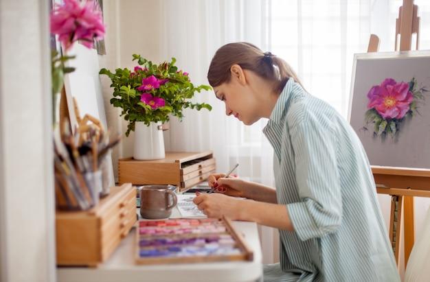 Vista lateral da artista desenha buquê de peônia rosa e rosa na mesa em seu local de trabalho sentado com caixas com giz de cera de pastéis secos e materiais para criatividade. conceito de criatividade e hobby