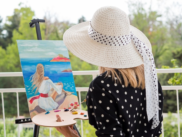 Vista lateral da artista feminina pintura com paleta