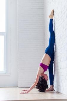 Vista lateral da atleta profissional praticando ioga, esticando as panturrilhas, isquiotibiais, coxas, fazendo exercícios de divisão em pé