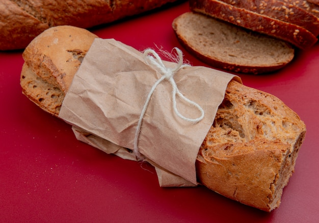 Vista lateral da baguete crocante com fatias de pão de centeio na superfície do bordo