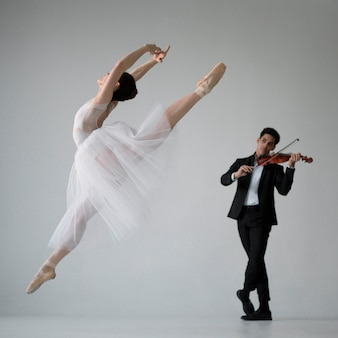 Vista lateral da bailarina com músico violino