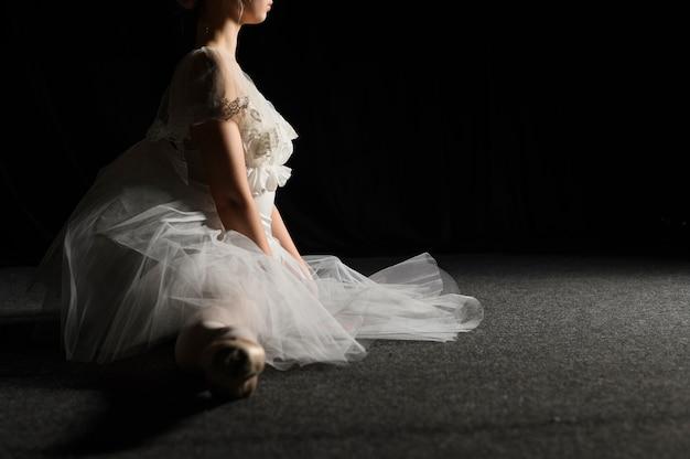 Vista lateral da bailarina com vestido tutu, fazendo uma divisão com espaço de cópia