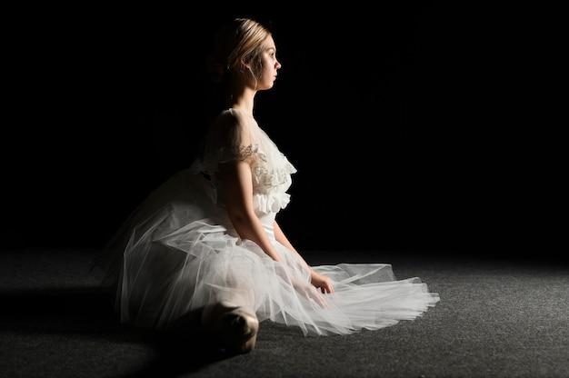Vista lateral da bailarina com vestido tutu, fazendo uma divisão