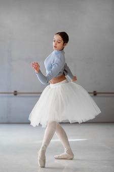 Vista lateral da bailarina dançando com saia tutu e sapatilhas de ponta