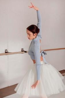 Vista lateral da bailarina dançando com saia tutu