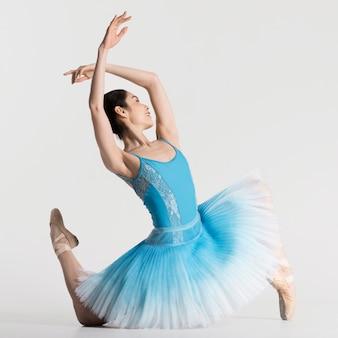 Vista lateral da bailarina dançando no vestido tutu