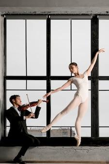 Vista lateral da bailarina e violinista posando