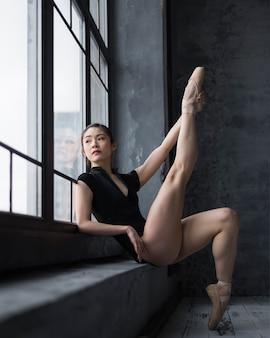 Vista lateral da bailarina em collant posando com a perna para cima