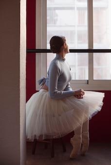 Vista lateral da bailarina em saia tutu ao lado da janela