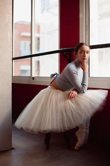 Vista lateral da bailarina em saia tutu posando ao lado da janela