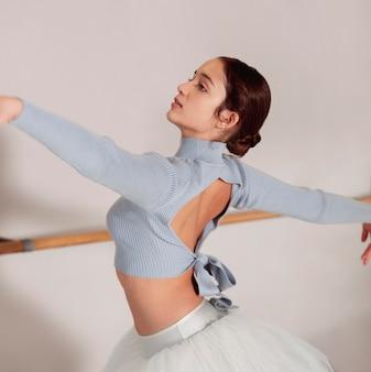 Vista lateral da bailarina ensaiando em saia tutu
