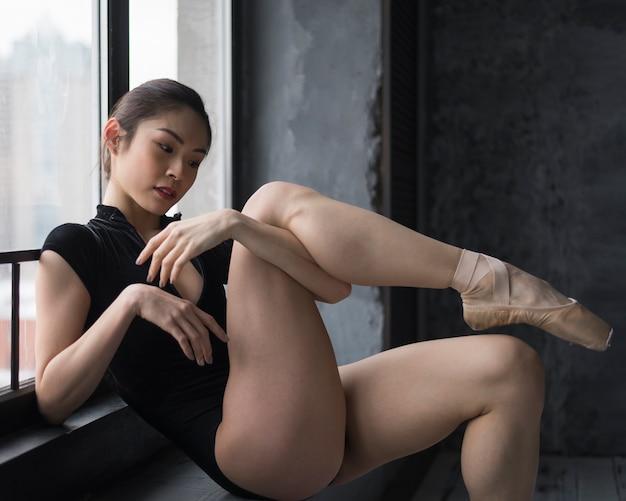 Vista lateral da bailarina pela janela posando
