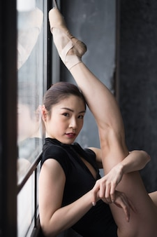 Vista lateral da bailarina posando com a perna para cima