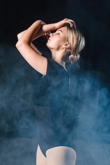 Vista lateral da bailarina posando com os braços na fumaça