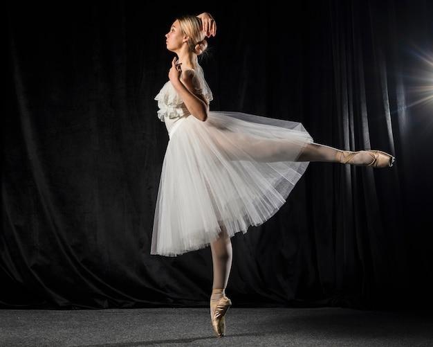 Vista lateral da bailarina posando em vestido de tutu