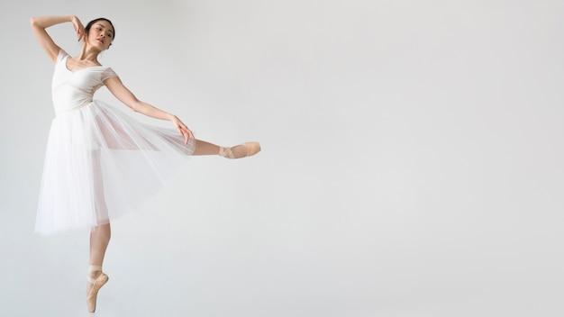 Vista lateral da bailarina posando em vestido tutu com espaço de cópia