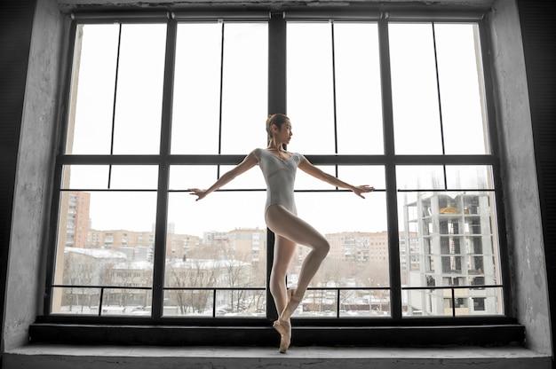 Vista lateral da bailarina posando pela janela