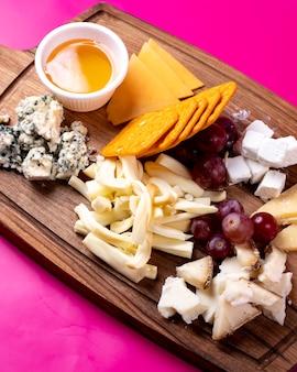 Vista lateral da bandeja de queijo com queijo cheddar feta parmesão