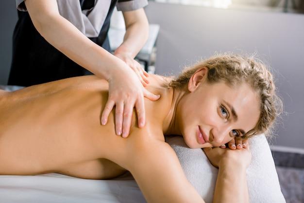 Vista lateral da bela jovem sorridente, recebendo massagem nas costas manual no centro médico moderno.